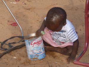 nina con lata de leche orfanato Burkina