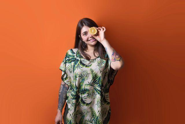 chica con fondo naranja y media naranja ocultando su ojo izquierdo