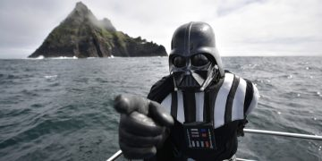 PORTMAGEE, IRELAND - MAY 04: A Star Wars fan dressed as the character Darth Vader takes a boat trip to the Skelligs on International Star Wars day May 4, 2018 in Portmagee, Ireland. The first ever Star Wars festival is taking place against the backdrop of the famous Skellig Michael island which was used extensively in Episode VII and Episode VIII of the popular science fiction saga. The small fishing village of Portmagee, which is closest to the location, has seen a boom in tourism following the latest films. The vilage will host a Star Wars drive-in and a Star Wars themed Irish dancing competition over the weekend. Today is known as 'May the fourth be with you' day. (Photo by Charles McQuillan/Getty Images)